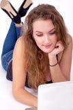 Ung härlig brunett som har online-shopping och att ligga ner som ser upp - Royaltyfria Foton