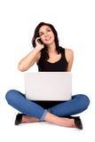 Ung härlig brunett som har online-shopping och att tala på telefonen som ser upp Arkivbild
