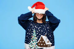 Ung härlig brunettflicka i knited tröja och julhatt som ler över blå bakgrund royaltyfri bild