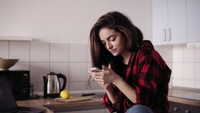 Ung härlig brunettflicka med smutsigt hår, i flanellskjortasammanträde i hennes kök och att smsa någon arkivfilmer