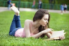 Ung härlig brunettflicka som läser en utomhus- bok royaltyfria bilder