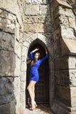 Ung härlig brunettkvinna för stående i den blåa klänningen som poserar mot bakgrunden av en gammal slott i den gotiska stile royaltyfri bild