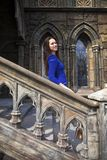 Ung härlig brunettkvinna för stående i den blåa klänningen som poserar mot bakgrunden av en gammal slott i den gotiska stile royaltyfri foto