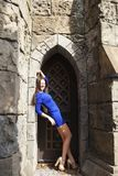 Ung härlig brunettkvinna för stående i den blåa klänningen som poserar mot bakgrunden av en gammal slott i den gotiska stile royaltyfria foton