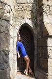 Ung härlig brunettkvinna för stående i den blåa klänningen som poserar mot bakgrunden av en gammal slott i den gotiska stile arkivbild