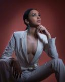 Ung härlig brunettkvinna i elegant vit dräkt med att sitta för byxa Förförisk flicka för mörkt hår som poserar, studioskott elega Royaltyfri Fotografi