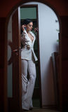 Ung härlig brunettkvinna i elegant vit dräkt med byxa som står i dörrram Förförisk flicka för mörkt hår som inomhus poserar arkivbild