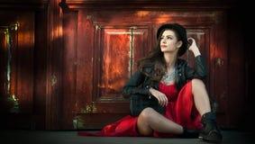Ung härlig brunettkvinna med att posera för röd kort klänning som och för svart hatt är sinnligt i tappninglandskap Romantisk mys royaltyfri fotografi