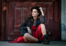 Ung härlig brunettkvinna med att posera för röd kort klänning som och för svart hatt är sinnligt i tappninglandskap Romantisk mys arkivfoton