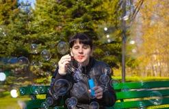 Ung härlig brunettkvinna som blåser bubblor arkivfoto