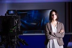 Ung härlig brunetttelevisionhallåman på studion under levande radioutsändning Kvinnlig TVdirektör på redaktören i studio Arkivbild