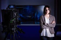 Ung härlig brunetttelevisionhallåman på studion under levande radioutsändning Kvinnlig TVdirektör på redaktören i studio Royaltyfria Bilder