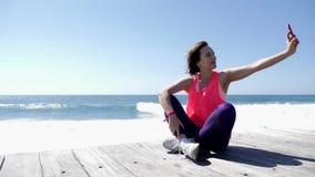 Ung härlig caucasian kvinna som sitter på innehavtelefonen för stenig strand och tar selfies Starka vågor som plaskar mot roen lager videofilmer