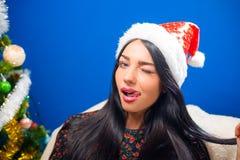 Ung härlig dam i jultomtenhatt som blinkar och Arkivbild