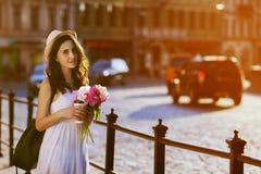 Ung härlig dam som går på gatan och att rymma den pappers- koppen med kaffe och buketten av pioner Bära för modell som är stilful Royaltyfri Foto