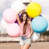 Ung härlig daminnehavgrupp av ljusa ballonger Royaltyfri Bild