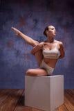Ung härlig dansare i beige swimwear som poserar på Royaltyfri Bild