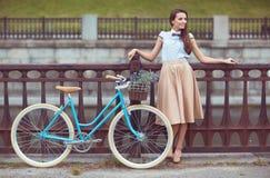 Ung härlig, elegantly klädd kvinna med cykeln
