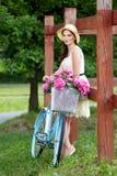 Ung h?rlig, elegantly kl?dd kvinna med den retro cykeln Sunt och att cykla royaltyfria foton