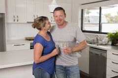 Ung härlig förälskade par30-tal eller 40-tal fira tillsammans årsdag eller valentindag med champagne- eller vinrostat bröd hemma Royaltyfri Foto