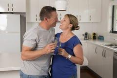 Ung härlig förälskade par30-tal eller 40-tal fira tillsammans årsdag eller valentindag med champagne- eller vinrostat bröd hemma Fotografering för Bildbyråer