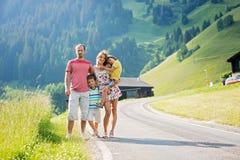 Ung härlig familj som reser i schweiziska fjällängar arkivbilder