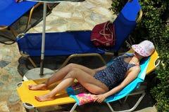 Ung härlig flicka i baddräkten och hatten som solbadar på en sommardag på en dagdrivare vid pölen Arkivfoton