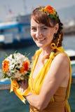 Ung härlig flicka i den ljusa orange bruden på en bakgrund av sjön Sommarbuketten räcker in royaltyfria bilder