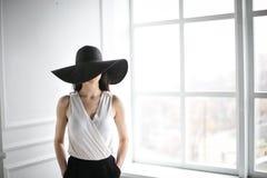 Ung härlig flicka i den stora svarta hatten Flickan sitter elegantly i en vit stol Royaltyfria Bilder