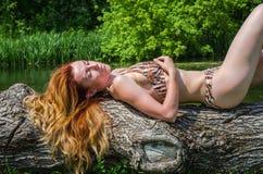 Ung härlig flicka i en baddräkt som ligger på ett träd på banken av den soliga sommardagen för flod fotografering för bildbyråer