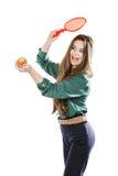 Ung härlig flicka i en grön blus som rymmer ett äpple med le för tennisracket Apple önskar att slå racket isolate Arkivfoto