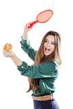 Ung härlig flicka i en grön blus som rymmer ett äpple med le för tennisracket Apple önskar att slå racket isolate Royaltyfri Foto
