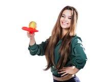Ung härlig flicka i en grön blus som rymmer ett äpple med le för tennisracket Apple önskar att slå racket isolate Arkivfoton