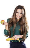 Ung härlig flicka i en grön blus som rymmer ett äpple och en banan och le isolate Arkivfoton
