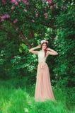 Ung härlig flicka i en krans av blommor i trädgården Royaltyfri Bild