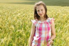 Ung härlig flicka i en veteåker Arkivfoton