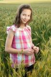 Ung härlig flicka i en veteåker Arkivfoto