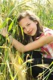 Ung härlig flicka i en veteåker Arkivbild