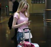 Ung härlig flicka i ett väntande rum i en flygplatsbyggnad som ser i en mobiltelefon Royaltyfri Foto