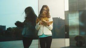 Ung härlig flicka i exponeringsglas som läser en bok lager videofilmer