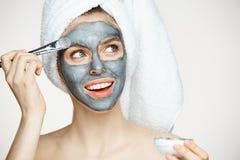 Ung härlig flicka i handduk på framsida för head beläggning med maskeringen som ler över vit bakgrund Skönhetcosmetology och brun royaltyfri bild