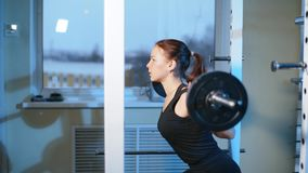 Ung härlig flicka i idrottshallen som gör övningar på det satt med en skivstång som förbättrar musklerna av bakdelarna och lager videofilmer