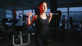 Ung härlig flicka i idrottshallen som gör övningar på det satt med en skivstång som förbättrar musklerna av bakdelarna och arkivfilmer