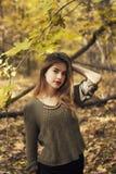 Ung härlig flicka i mitt av höstsidor i bakgrunden Arkivfoto