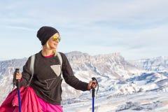 Ung härlig flicka i solglasögon med nordiska poler i solnedgångljuset på bakgrunden av den Caucasian kanten Royaltyfri Fotografi