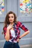Ung härlig flicka i stilfull kläder som poserar i stadsgatan arkivbilder