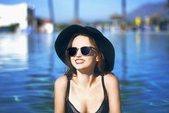 Ung härlig flicka i svart modehattleende, sammethud, röda kanter, svart baddräkt som poserar i pölen i blått vatten Arkivfoton