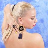 Ung härlig flicka i svarta örhängen på en abstrakt bakgrund Royaltyfri Fotografi