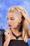 Ung härlig flicka i svarta örhängen på en abstrakt bakgrund Royaltyfria Bilder