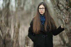 Ung härlig flicka i svarta exponeringsglas för en lagblåtthalsduk som går i hösten/våren Forest Park En elegant brunettflicka med Royaltyfri Foto